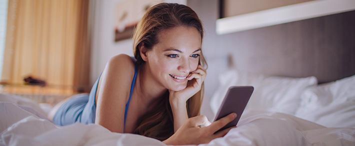 Online flirten - Frau liegt mit Smartphone auf einem Bett