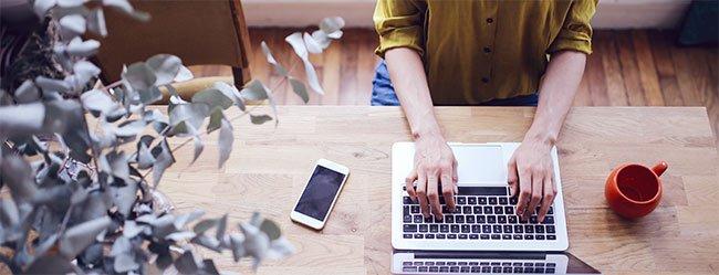 Partner Shopping dargestellt durch Vogelperspektive auf Schreibtisch an dem Frau an ihrem Laptop auf Partnersuche ist