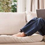 Frau fühlt sich sicher bei der Partnersuche mit ElitePartner und sitzt zufrieden mit Laptop auf dem Schoß auf dem Sofa