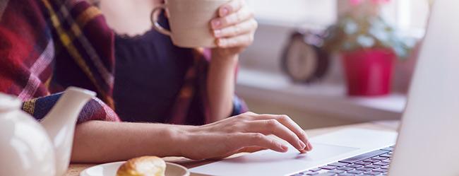 Frau am Laptop versucht den Widerruf bei ElitePartner durchzuführen