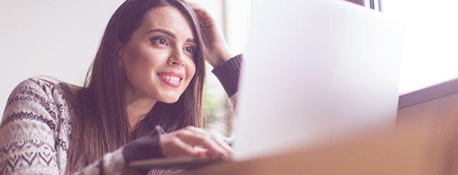 Frau sitzt gespannt am Laptop und spührt die Sicherheit bei der Online Partnersuche