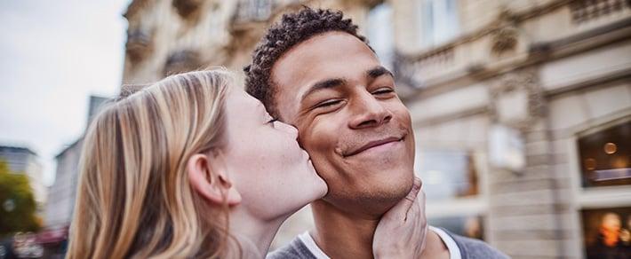 Frau küsst Mann auf die Wange als Symbol für Wangenkuss