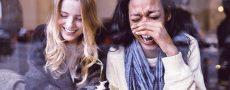 Zwei Frauen amüsieren sich hinter der Fensterscheibe eines Cafés als Darstellung der Generation Y gegenüber Beziehungen