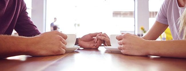 Nach der Beziehungspause: Mann und Frau am Tisch gegenüber sitzend für Beziehungsgespräch