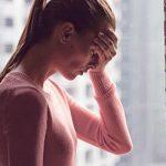 Frau steckt in Liebeskummer und berührt verzweifelt ihre Stirn