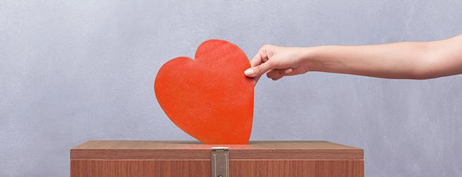 Herz wird in Wahlbox gesteckt als Symbol für die Ergebnisse der ElitePartner Wählerstudie 2017