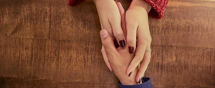 Neue Beziehung nach Trennung: Frau im Auto hält sich symbolisch am arm Ihres neuen Partners fest