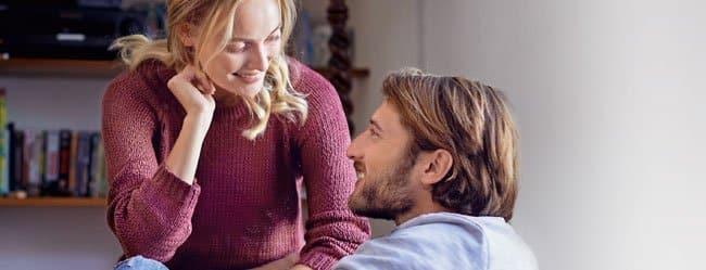 Akademische Partnersuche: Frau sitzt Mann auf Schoß und sie lächeln sich an