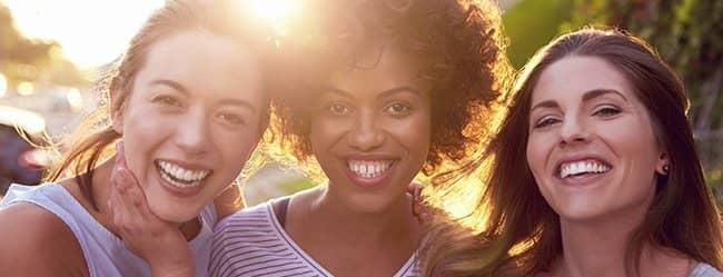 Drei Frauentypen lächeln in die Kamera
