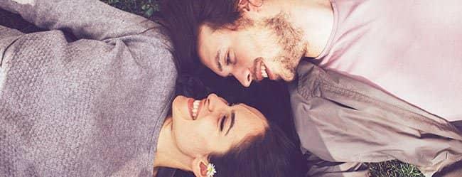 Mann und Frau liegen auf dem Rasen und sind frisch verliebt