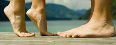 Ausschnitt Füße Mann und Frau auf Zehenspitzen als Symbol für große Männer