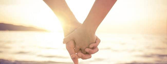 Zwei Menschen halten Händchen als Symbol für karmische Liebe