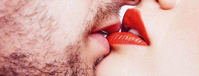 Mann mit Bart küsst Frau mit rotem Lippenstift richtig