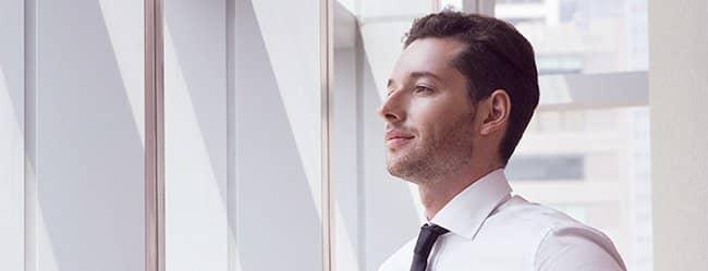 Mann mit Hemd und Krawatte schaut arrogant und signalisiert Macho-Verhalten