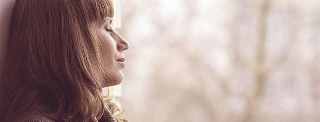 Frau mit geschlossenen Augen am Fenster ist in Midflife Crisis