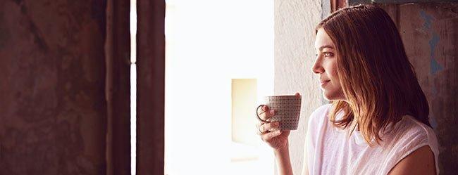 Neurotiker: Frau trinkt Kaffee und schaut aus dem Fenster