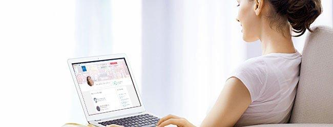 Frau mit Laptop auf dem Schoß sucht ihren Partner im Internet