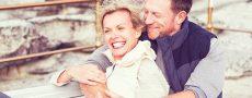 Partnersuche ab 60 erfolgreich: Paar ü60 sitzt aneinander gekuschelt auf Plattform
