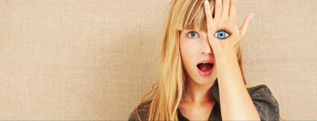Frau ertappt sich beim Selbstbetrug und schaut mit Hand auf einem Auge erschrocken in die Kamera