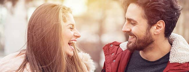 """Mann lacht Frau an - ein Symolbild für die Frage: """"Wie verlieben sich Frauen?"""""""