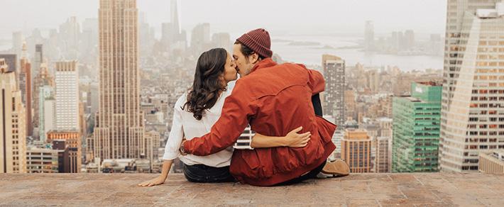Frau und Mann küssen sich über Wolkenkratzern, als Symbol für internationale Partnersuche usa