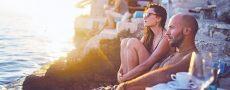 Urlaubsmythen symbolisch durch Paar im Urlaub das Sonnenuntergang an einer Klippe anschaut