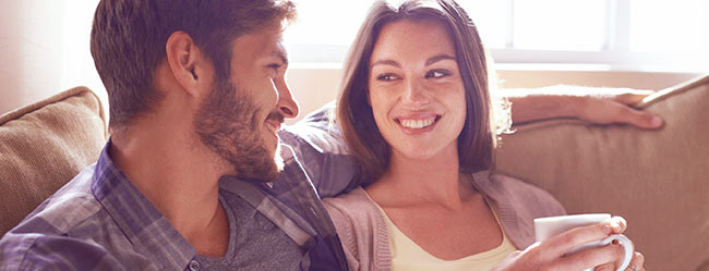 Mann und Frau auf Couch im Beziehungstest