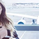 Frau steht am Flughafen mit Handy um falschen Mann zu erkennen
