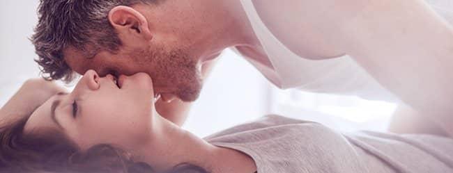 Mann will Frauen verführen und küsst sie am Nacken