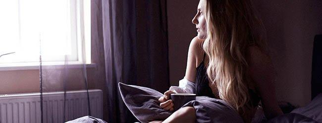 Frau sitzt verzweifelt im Bett und blickt aus dem Fenster um herauszufinden wie sie Trennung verarbeiten kann