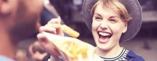 """Frau ärgert Mann mit Pommes in der Hand als Symbol für """"Was sich neckt, das liebt sich"""""""