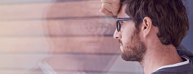 Mann lehnt verzweifelt mit Stirn an der Fensterscheibe und denkt über die Ängste in einer Beziehung nach