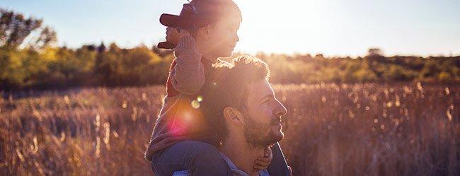Emotionaler Mann in Gerstenfeld mit Kind auf seinen Schultern