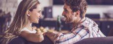 Frau und Mann sitzen sich auf Couch gegenüber und versuchen ihr Gegenüber zwischen Anspruch und Wirklichkeit zu wählen