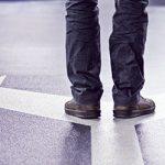 Mann steht auf Straße als Symbol dafür, dass er sich zurückzieht