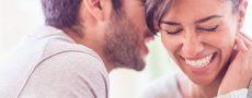 Mann flüstert einer Frau Komplimente ins Ohr