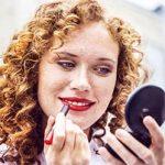 Frau geht fremd und trägt sich Lippenstift mit einem Spiegel in der Hand auf