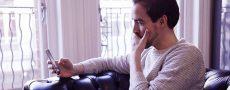Mann fragt sich wie er Geühle zeigen kann und sitzt rätselnd auf der Couch vor seinem Handy