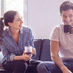 Ein Paar trinkt zu Hause einen Kaffee, er schaut unsicher zu Boden