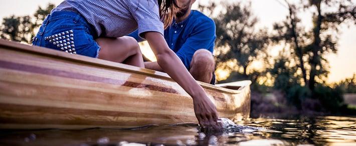 Mann und Frau fahren Kanu als Date-Idee für den Sommer