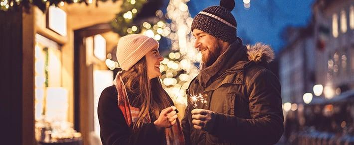 Mann und Frau mit Wunderkerzen als Symbol für Date-Ideen im Winter