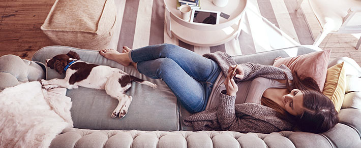 Single-Frau entspannt auf dem Sofa