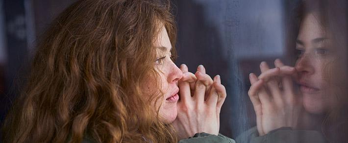 Frau schaut aus dem Fenster, überlegt wie sie Ex zurückgewinnen kann