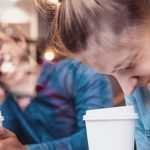 Mann und Frau lachen gemeinsam im Café beim Slow Dating