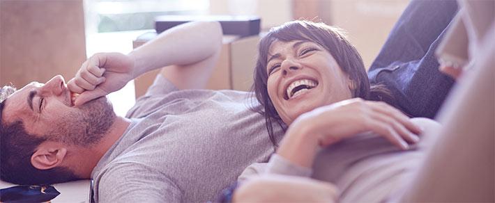 Ein Paar hat sich kennengelernt und zieht jetzt zusammen, sie liegen lachend zwischen Umzugskartons